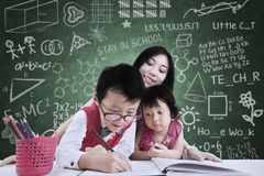 Boy and his sister study in class with teacher Royalty Free Stock Image