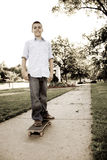 Boy On His Skateboard. A young teenage boy standing on his skateboard in the park.  Sepia tone Stock Image