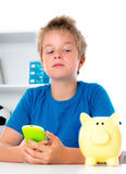 Boy with his smartphone and pggy-bank Royalty Free Stock Images