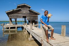 Boy and his starfish. Young black boy on Roatan displaying with pride his newly caught starfish Royalty Free Stock Photos