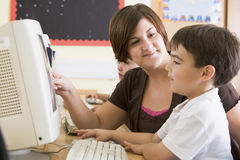 A boy and his teacher working on a computer Stock Image