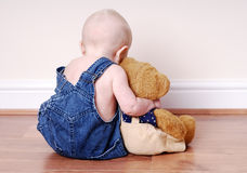 Boy and his teddy. Baby boy (7 months old) in blue jean overalls hugging his bear.  He's sitting on a wood floor, and facing away from the camera.  A very sweet Stock Image