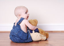 Boy and his teddy. Baby boy (7 months old) in blue jean overalls hugging his bear.  He's sitting on a wood floor, and facing away from the camera.  A very sweet Stock Photography