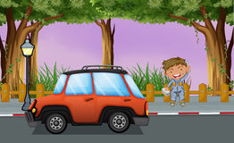 A boy with his tools near the orange vehicle Royalty Free Stock Image
