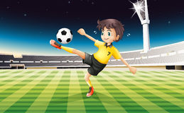 A boy in his yellow uniform playing soccer at the field Royalty Free Stock Photography