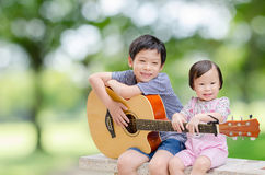 Boy and his younger sister in garden Stock Photography
