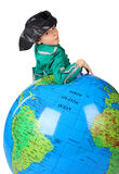 Boy in historical dress leans on inflatable globe Royalty Free Stock Photo
