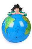 Boy in historical dress leans on inflatable globe Royalty Free Stock Image