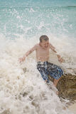 Boy hit by wave. A boy getting hit by a wave in the ocean Stock Image