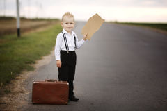 Boy hitch hiking at road Royalty Free Stock Image