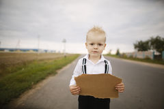 Boy hitch hiking at road Royalty Free Stock Photo