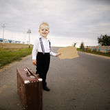 Boy hitch hiking at road Royalty Free Stock Photography