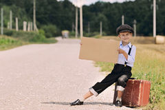 Boy hitch hiking on the road Royalty Free Stock Photography