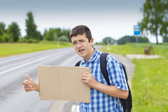 Boy hitchhiker on the road waiting for car to stop. In summer Royalty Free Stock Photos