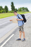 Boy hitchhiker on the road waiting for car to stop. In summer Stock Photos