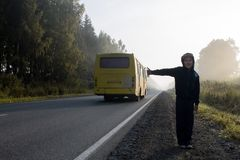 The boy is hitchhiking on the road. A boy in a dark hooded sweatshirt hitchhiking on a forest road in a fog Stock Photo