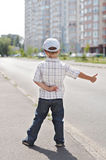 Boy hitching on road Stock Photography