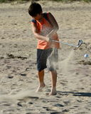 Boy hits a golf ball at the beach. A 10 years old boy enjoys hitting the golf club  at the beach Stock Photo