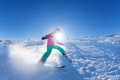 Boy hitting down a slope on ski race at sunny day Royalty Free Stock Photography