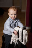 Boy on hobby horse. Cute young boy riding hobby horse in house royalty free stock images