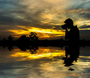 Boy hold camera silhoutte with orange skies Royalty Free Stock Photo