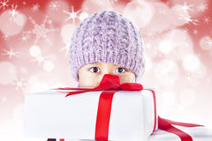 Boy hold gifts on red defocused lights background Royalty Free Stock Image