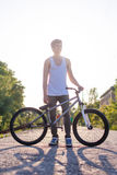 The boy hold his bike, photo at sunrise background Royalty Free Stock Photography