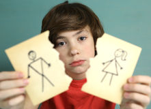 Boy hold mom and dad drawing torn apart. Preteen handsome boy hold mom and dad drawing torn apart with sad expression close up photo royalty free stock image