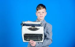 Boy hold retro typewriter on blue background. What to do with this thing. Out of date. I need modern gadget instead this. Retro. Outdated gadget. Retro and royalty free stock photography