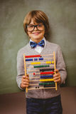 Boy holding abacus in front of blackboard Stock Images