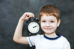 Boy holding alarm clock. Stock Photo