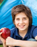 Boy Holding Apple At Campsite Royalty Free Stock Photography
