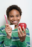 Boy holding apple and toothbrush Royalty Free Stock Photography