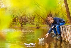 Boy holding arm to play with white paper boats Royalty Free Stock Image