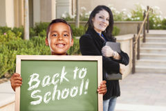 Boy Holding Back To School Chalk Board with Teacher Behind Stock Photography