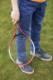 Boy holding badminton racquet while standing on green grass. Cropped shot of boy holding badminton racquet while standing on green grass stock image