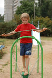 Boy holding a balance. Walking on the board with a stick in the playground Stock Image