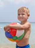 Boy holding ball on the beach Stock Image