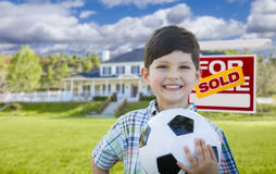 Boy Holding Ball In Front of House and Sold Sign Stock Photography