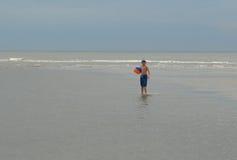Boy holding ball on sea beach Stock Photos