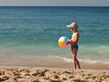 Boy holding ball on sea sand beach Royalty Free Stock Photo