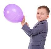 Boy holding a balloon. Smiling little boy holding the balloon isolated on white background stock photography