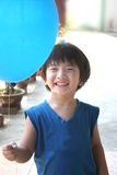 Boy holding balloon. Boy with blue singlet holding blue balloon Royalty Free Stock Image