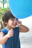 Boy holding balloon with victory hand sign. Boy with blue singlet holding blue balloon with victory hand sign stock image