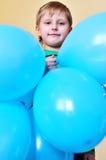 Boy holding balloons stock photography