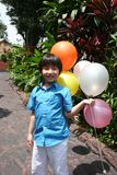 Boy holding balloons. Boy smiling and holding colorful balloons on a sunny day Stock Images