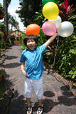 Boy holding balloons. Boy smiling and holding colorful balloons on a sunny day Stock Photography