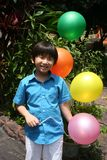 Boy holding balloons. Boy smiling and holding colorful balloons on a sunny day Royalty Free Stock Image