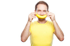 Boy holding banana like his smile. Boy in yellow t-shirt holding with his hands banana near his face like a smile stock photo