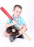 Boy holding a baseball bat with ball and glove. Young boy biting his lip holding a baseball bat with ball and glove Royalty Free Stock Photo
